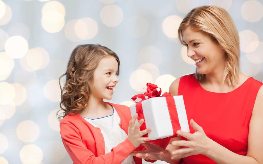 little girl handing her mom a christmas present