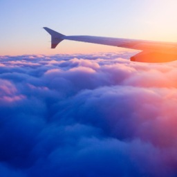 pic of plane wing while flying over the clouds into the sunrise