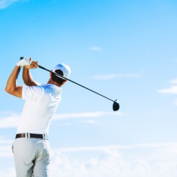man mid golf swing on a clear day