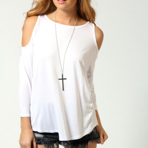 Woman in cut out shoulder top shirt wearing crucifix necklace