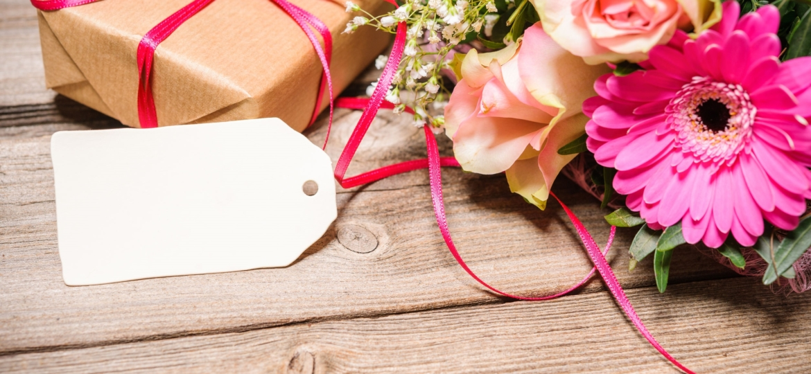 Gift wrapped on wooden table with flowers.