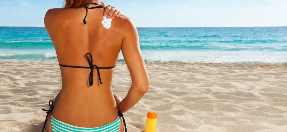Woman putting on sun tanning lotion on the beach.