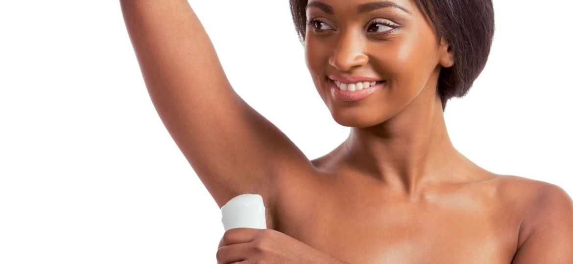 Pretty African American woman putting on deodorant