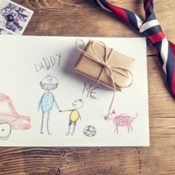 Picture of kids on white paper. Father's tie laying on table and a small wrapped gift.