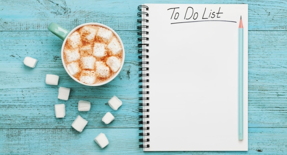 cup of hot cocoa or chocolate with marshmallow and notebook with to do list on turquoise vintage table from above, christmas planning concept. flat lay style.