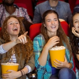 Three girls at the movie eating popcorn.