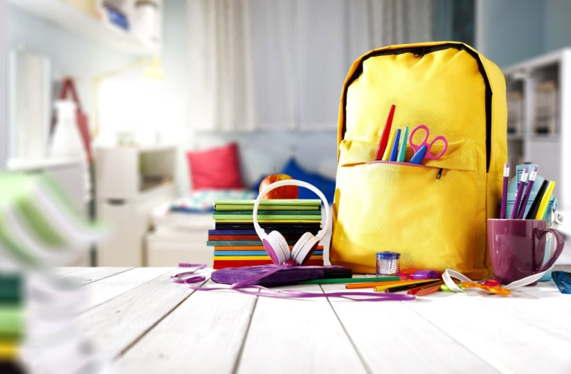 Child's room with a yellow bookbag and school supplies on the desk