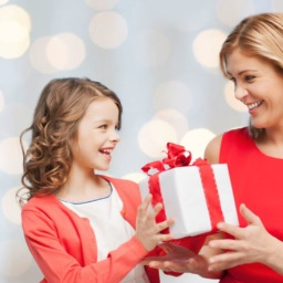 little girl handing her mom a christmas present