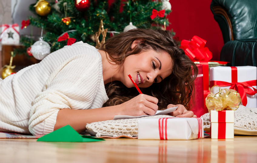 woman lying on floor beside the christmas tree writing her christmas list