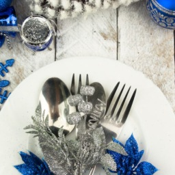 white plate and silver cutlery with blue and silver table setting decorations