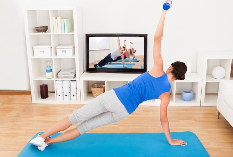 woman watching a workout video in her livingroom and doing a side plank on her yoga mat