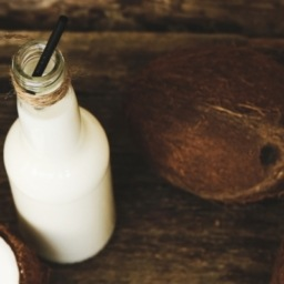homemade coconut kefir in a bottle sitting on a wooden table beside a coconut