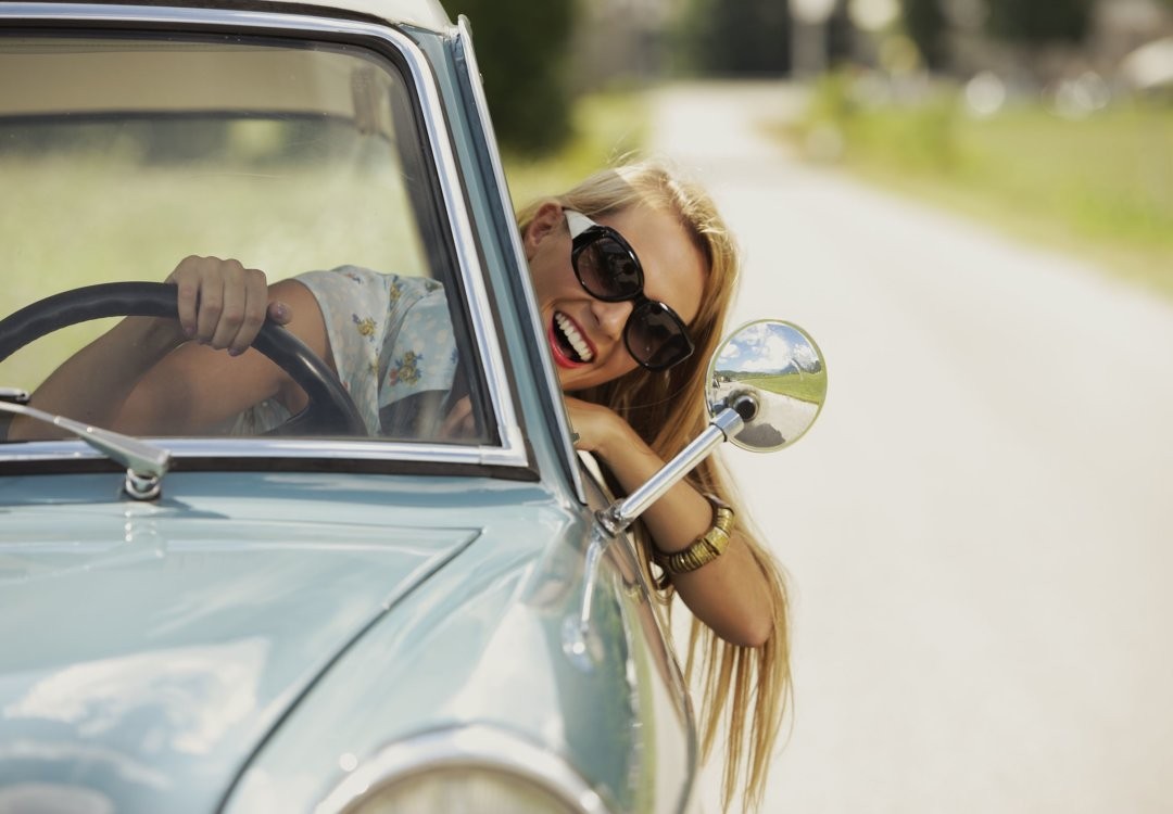 girl driving while hanging her head out the window, wearing sunglasses and smiling