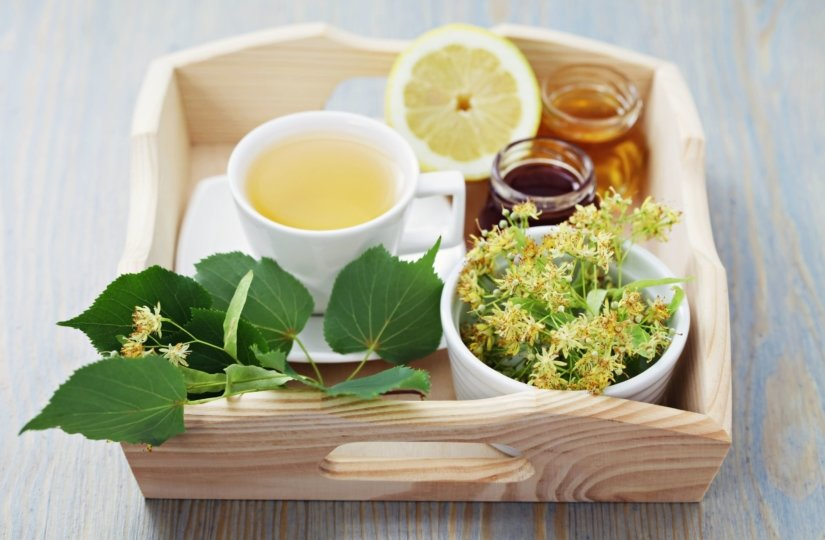 wooden tray holding a mug of green tea, a lemon, a jar of honey and a bowl of wildflowers