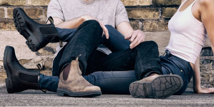 man and woman sitting on the ground wearing jeans and blundstones