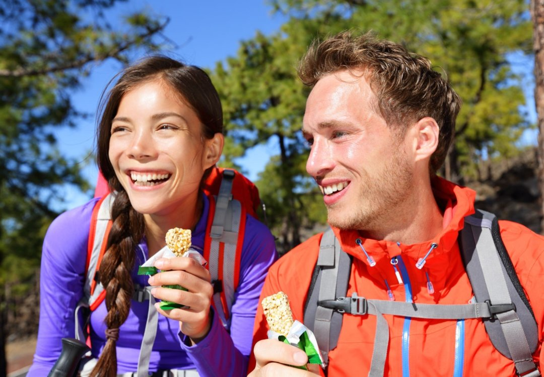 Man and woman hiking and eating a protein bar while hiking