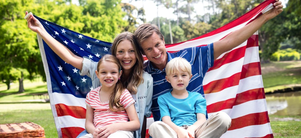 Man with American flag wrapped around his family