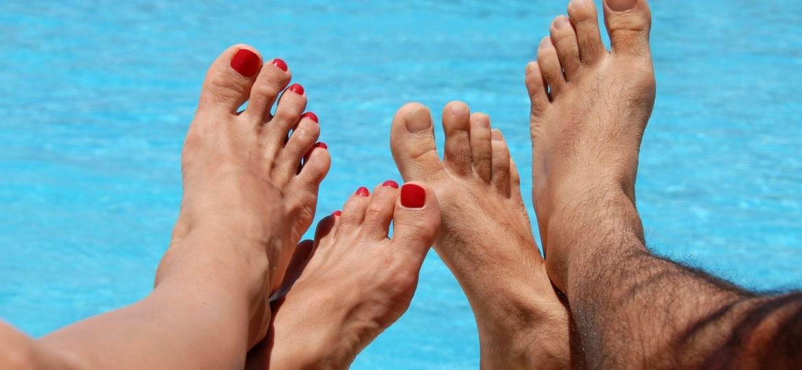 Man and woman feet by poolside