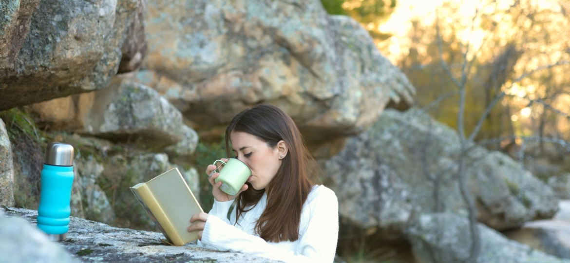 Woman drinking tea in the woods.