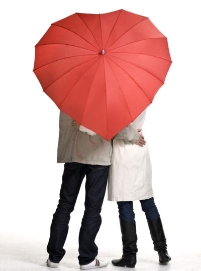 Couple under heart-shaped umbrella