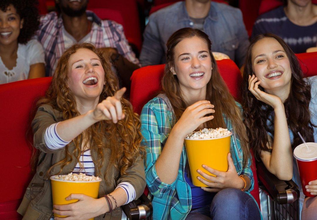 Three girls at the movie eating popcorn.