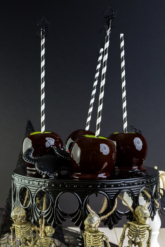 Black candy apples on a black halloween cake stand